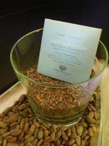 """Une tablette """"Carré 2 Chocolat"""" au milieu de fèves de cacaco Photo Bettina Aykroyd"""